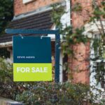 An estate agent's for sale sign outside of a house