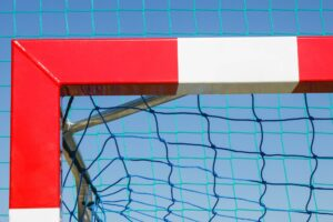 Football or handball goal with red and white goalpost