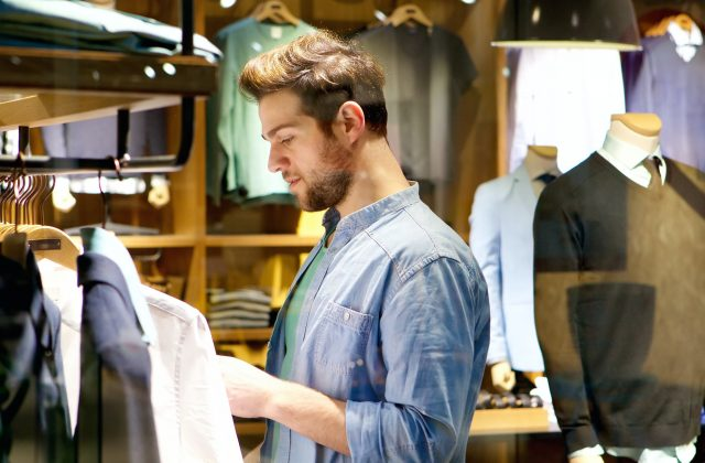 Mandsome young man shopping for clothes at shop