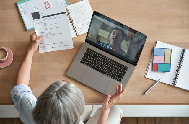 Senior woman employer hr holding job interview by video call, top view.